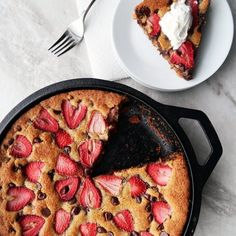 A large strawberry chocolate chip cookie baked in a cast-iron skillet to create puffed, crispy edges and a soft, chewy center!