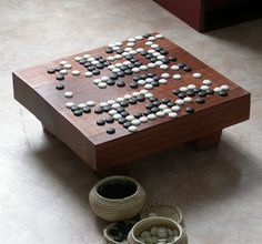 Nice little Goban.  Or Go Board.  I will be building one of these some day.  Traditionally, they are constructed of a single piece of the japanese Kaya tree.  They are as well much deeper; built with hexagonal legs and stained a natural light tone.  I think I prefer the colour of this one though!  Great inspiration and a great game.  :)