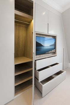 Bespoke joinery unit with timber lined TV recess. Handless sprayed doors and veneered wardrobe carcassing to match the TV recess.