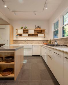 High gloss white cabinets paired with concrete countertops and custom plywood raw steel shelves.