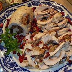 "Cranberry Stuffed Turkey Breasts | ""These beautiful spiraled medallions are created by rolling bread stuffing, dried cranberries and chopped pecans in butterflied turkey breasts. Each roll is browned in butter and baked before slicing."""