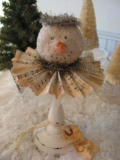 Paper Mache Snowman.  I bet a Styrofoam ball would work just as well - paint it a pale beige and cover with mica glitter.  Looks like a pleated book page as a collar, and a candlestick for a base.