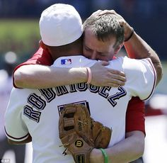 The heartwarming and heartbreaking moment the father of a child killed in Newtown embraces his Texas Rangers baseball hero before making the ceremonial first pitch in honor of his 6-year-old daughter, Emilie,  who was killed in the mass school shooting in Newtown, Conn.