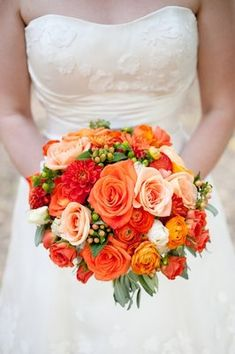 Dahlias, orange ranunculus, and berries. I like this for a late summer or fall wedding.