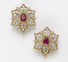 A pair of ruby and diamond clip-earrings, Buccellatti, Italy of stylized floral design, each earring centering an oval-shaped ruby, surrounded by round brilliant-cut diamonds within a leaf motif, accented by carved gold borders; signed Gianmaria Buccellati, no. Z2617, Italian assay marks; estimated total diamond weight: 1.15 carats; mounted in bicolor eighteen karat gold.