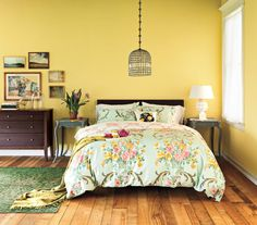 Bright walls, a floral duvet, and furniture with feminine touches give this bedroom a cozy, country feel.