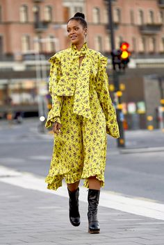 Rihanna looking amazing in a yellow floral dress with awkward height black boots in Stockholm.