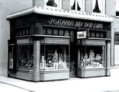 1930's. A view of a neoclassic-style façade of a liquor store at Overtoom number 71 in Amsterdam-West. Today this is a Domino's pizza store. The Overtoom is a street that connects the Stadhouderskade with the Amstelveenseweg. In the 1800's the street was a canal that, after the construction of the Jacob van Lennepkade, was filled-in in 1904, making it a wide exit route, originating at the Leidseplein, to the Amstelveenseweg. Photo Stadsarchief Amsterdam / Jan van Dijk. #amsterdam #1930…