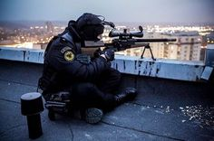Member of the Lithuanian counter-terrorist unit ARAS on a rooftop conducting surveillance