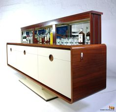 Check out this marvellous James Bond style rosewood electric bar      c.1960 by Deconet  Description: deluxe for your living room. here comes an incredible /  handcrafted '60s rosewood sideboard with curved edges and an electric bar  inside. this credenza fits very good to furniture from willy rizzo, jacques  duval brasseur & maison charles / provenance: probably germany / material:  rosewood, mirrors, white-/creme plastic sheathed front, electric mirrored  bar. the unit is in working con...
