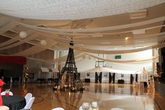 Transforming a gym into A Prom. drape table runners on a fish line up and down for walls