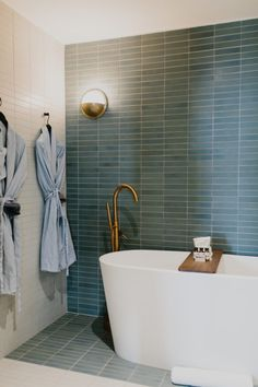 Wall to wall stacked floor tile and brass fixtures in this master bathroom at the South Congress Hotel
