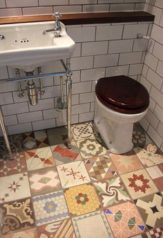 Mismatched tiles in a cohesive color palette/style. Cool :) Something to look at instead of magazines! Ha ha! Love it!