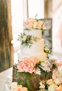 A three-tiered white wedding cake covered in blush blooms by Virginia's Cakes, sitting on a tree stump cake display.