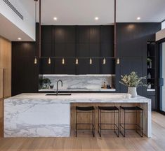 in this kitchen, someone's eyes are drawn to the marble island first as it is contrasted against the black walls behind it. finally, the viewer notices the plant that is upon the countertop as the green in the leaves stand out.