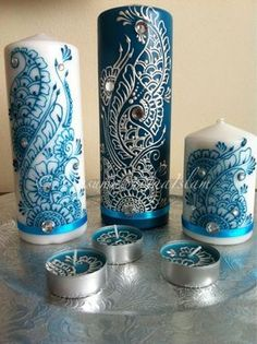 Henna Art Candles - Tutorial not included in article. I would take any candle of choice, scented/non scented, either use delicate  paint brush or a henna paste tube (looks like a mini cake icing tube), and decorate. Just stick the gems on with henna.