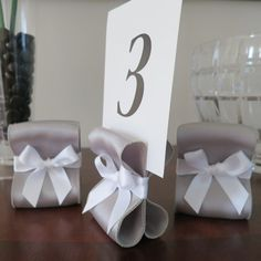 DIY Idea! or buy them- Table Number Holders - Wedding Decor - Set of Ten (10) with Silver and White Satin Ribbon - Customize Your Colors. $35.00, via Etsy.