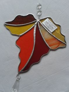 Maple leaf sun-catcher, choose from: (a) autumnal orange, reds and ambers (b) a vibrant mix of greens (c) clear texture glass and opaques Hung from invisible thread with 3 clear glass faceted jewels for that extra bit of sparkle! Glass measures 190mm x 170mm approx