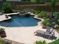 Residential Pool #013 - Freeform Pool and Spa with stamped concrete decking. Features include: raised spa with stacked stone spillway, sunshelf with custom bench, Oklahoma flagstone coping, stamped concrete decking with area drains to the street, detailed landscape package.
