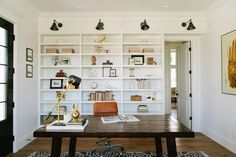 House of Jade Interiors transformed this home office into a stunning space with stark white walls, built-in white bookshelves and a farmhouse wood desk. Burnt orange and gold accents are a nice complement to the clean color palette.