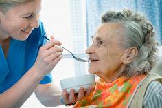 De bejaardenverzorgster verzorgt deze oudere dame door haar eten te geven. Juf Pien