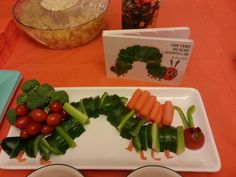 The Very Hungry Caterpillar Veggie Tray. I used a cucumber, Green bell pepper, celery, carrots, tomatoes, and raisins for the eyes (put a toothpick through the tomato to keep it in place)  Fun babyshower theme.