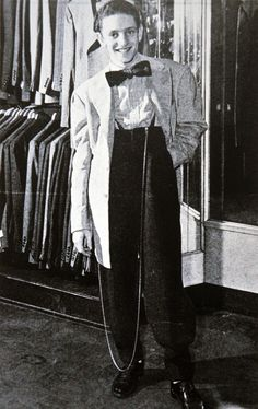 The American Zoot Suit, c.1939: The zoot suit is a suit with high-waisted, tight-cuffed, pegged trousers and a long coat with wide lapels and wide padded shoulders; it was popularised by African Americans, Latino Americans, Italian Americans and Filipino Americans during the 1930s and 1940s;