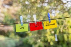 Life Is Beautiful concept with the words hanging on three green red and yellow cards from a clothes  Stock Photo