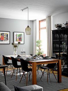 Ruokatila on aivan keittiön vieressä. Tilan seinistä poistettiin tapetti ja ne maalattiin harmaalla. Suuri pöytä on puusepän tekemä ja mustat Eamesien DSW-tuolit hankittiin Vepsäläiseltä.