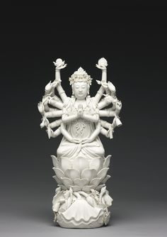 A DEHUA MULTI-ARMED FIGURE OF GUANYIN QING DYNASTY, 19TH CENTURY seated dhyanasana on top of a lotus base with overlapping petals, above swirling waves applied further with lotus stems bearing buds and large curling leaves, the primary hands held in anjalimudra, the lower pair in dhyanamudra, the other fourteen hands extended holding various attributes, the back with a double-gourd seal reading Dehua, and a square seal below reading He Chaozong zhi 15 1/4  in., 38.8 cm 7/9000