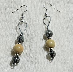 These wire-wrapped earrings vaguely remind me of a riverbank or a coastline. The shimmering of the darker beads is like a shimmering river and the lighter beads are a sandy colour.