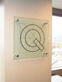 "Qualitect Q - Square Glass Sign - SIGN  Technique:  CARVED & PAINTED  Specifications:  24"" x 24"" x 1/2"" Clear Tempered Glass, mounted with Brushed Nickel Stand Off Posts"