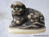 Ivory netsuke with a shishi. Very well carved marine ivory netsuke with a shish on a base. it has the look of a Rensai school depiction of a shishi.. Size 26mm high- 37mm wide. Late 18th Early 19th C Code : 615