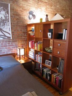 Love the ikea bookshelf as space divider -- on wheels! Leslie's Little Loft | Small Cool 2011 | Apartment Therapy