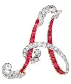 A Ruby and Diamond Brooch, circa 1920. Designed as the letter A, decorated with calibré-cut rubies, old European and rose-cut diamonds, mounted in platinum and 18k gold.