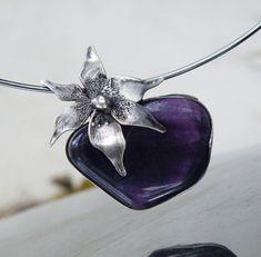 Květ ticha...(fluorit) Autorský cínový šperk s temně fialovým fluoritem... Velikost kamene je 3,3 x 2,5cm. Brava jetemně fialová - nádherný odstín, proti světlu je kámen průsvitný. Je usazen v cínu, zdoben cínovaným drátem a velkým, ručně vyrobeným cínovým květem. Celková velikost šperku je 4 x 3,8cm. Zavěšeno na pevné černé obruči o průměru 14cm. Patinováno,...