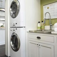 BHG - laundry/mud rooms - stackable washer and dryer, front loading washer, front loading dryer, white stackable washer and dryer, green walls, avocado green walls, gray floor tile, dark gray floor tile, charcoal gray tiled floors, marble countertops, stainless steel sink, shower head kitchen faucet, shower head faucet, oil rubbed bronze hardware, crystal hardware, striped rug, laundry room storage, laundry room, laundry rooms, white and green laundry room,