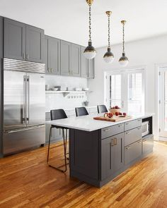 Charcoal gray kitchen boasts three small hicks pendants hung over a gray island fitted with gray cabinets and drawers donning brass pulls and holding a microwave in a shelf beneath a white quartz countertop seating three black counter stools on oak wood floors.