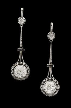 A pair of diamond pendent earrings, circa 1920 Each old brilliant-cut diamond, within a pierced collet setting, suspended from a smaller old brilliant-cut diamond by an engraved tapered baton and a synthetic sapphire bar, principle diamonds approximately 3.00 carats each, sapphires deficient, length 5.4cm
