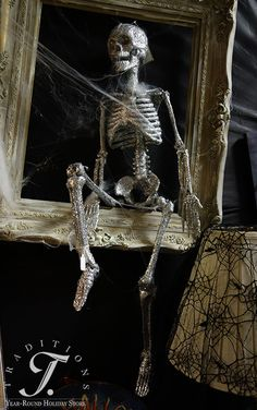 This glittered skeleton sits in a frame hanging on the wall.