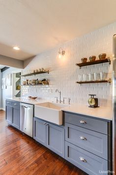 Subway tiles to ceiling, open reclaimed wood shelves, gray bottoms, farm sink.