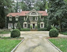 Ivy covered house, center driveway, boxwoods and clipped hedges