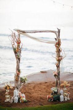 Flower adorned driftwood beach wedding arbor