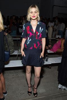 Bella Heathcote wears a floral silk button-down, miniskirt, and ankle-strap sandals