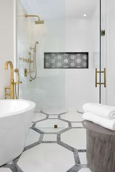 A corner oval bathtub is paired with a floor-mount brushed gold tub filler which is placed next to a seamless glass shower filled with a black and white hex tiled niche.