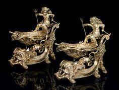 A PAIR OF VICTORIAN SILVER-GILT SALT CELLARS MARK OF ROBERT GARRARD II, LONDON, 1857 Each formed as a shell-shaped boat riding the waves, supported by two dolphins, steered by a winged sea-putto clasping a trident and tiller, with detachable liner, with two oar-shaped salt spoons