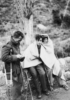 Fleeing Loyalists huddle under a blanket on the road to Perpignan during the Spanish Civil War, circa 1936.