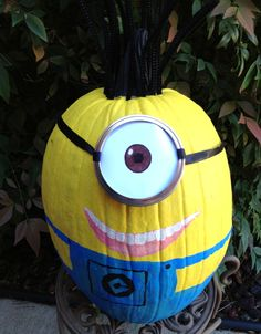 Our Minion Pumpkin for Halloween 2013 Painted a tall pumpkin yellow with blue overalls. Tied on a mason jar lid with black ribbon after creating an eye out of white paper and markers. Painted on a mouth and added black pipe cleaners for crazy hair. Easy and fun! Despicable Me.