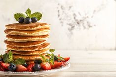 homemade pancakes with berries and fruit on a white background