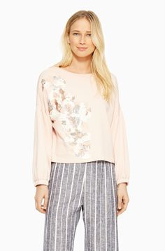 Our blush Berniece Top, with drop shoulders and a floral sequin applique, is cool girl–approved.